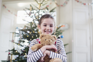 Portrait smiling, cute girl holding teddy bear in front of Christmas tree - HOXF03877