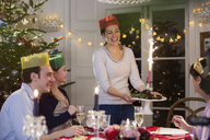 Smiling woman in paper crown serving Christmas pudding with fireworks to family at dinner table - HOXF03886