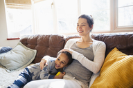 Affectionate mother and toddler son cuddling on living room sofa - HOXF03898