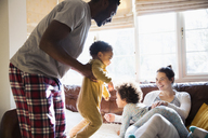 Playful multi-ethnic family in pajamas in living room - HOXF03931