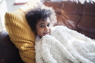 Portrait cute girl relaxing, cuddling on sofa with blanket and pillow - HOXF03940
