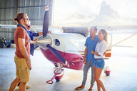 Friends talking at prop airplane in airplane hangar - CAIF21744