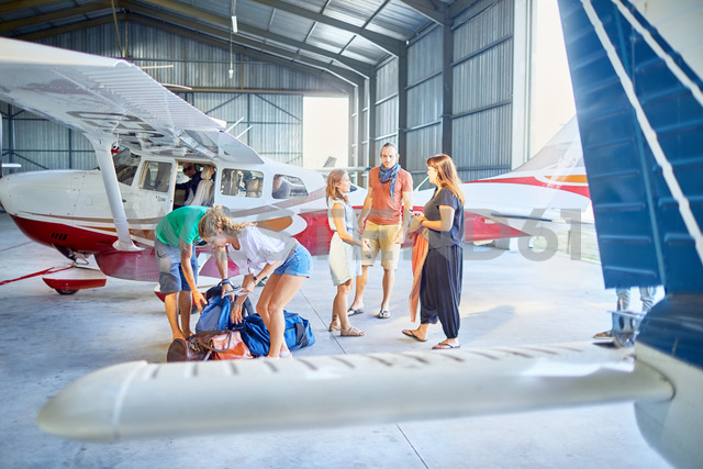 Friends preparing bags in airplane hangar - CAIF21747