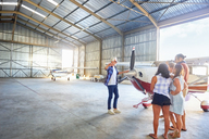 Pilot talking to friends at prop airplane in airplane hangar - CAIF21753
