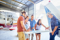 Friends planning trip at map in airplane hangar - CAIF21759