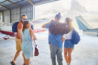 Friends with bags walking in airplane hangar - CAIF21762