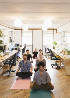 Serene creative business people meditating in office - CAIF21792