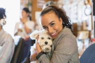 Portrait happy businesswoman with cute dog in office - CAIF21825