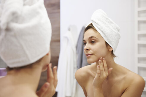 Mirror image of young woman examining her face in the bathroom - ABIF00984