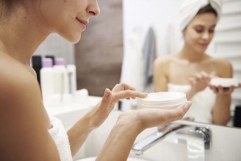 Young woman applying moisturizer in bathroom, partial view - ABIF00987