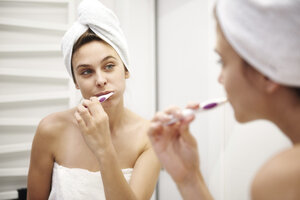 Mirror image of young woman in bathroom brushing her teeth - ABIF00990