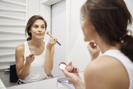 Mirror image of smiling young woman applying Makeup in bathroom - ABIF00999