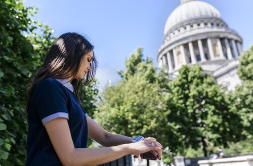 UK, London, young woman using her smartwatch near St. Paul's Cathedral - MGOF03776