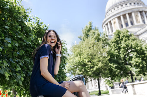 UK, London, laughing young woman talking on the phone near St. Paul's Cathedral - MGOF03779