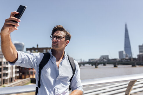 UK, London, man taking a selfie on Millennium Bridge - MGOF03785