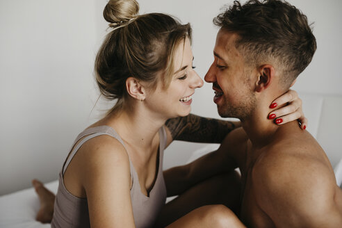 Happy young couple in bed smiling at each other - LHPF00031