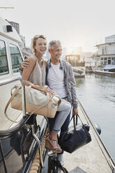 Older man and young woman standing with travelling bags on jetty next to yacht - RORF01550