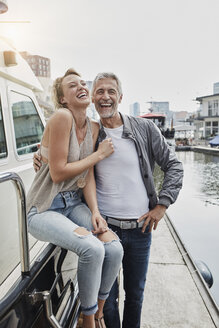 Laughing older man and young woman standing on jetty next to yacht - RORF01553