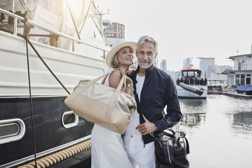 Older man and young woman standing with travelling bags on jetty next to yacht - RORF01556