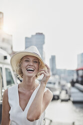 Portrait of laughing young woman wearing a hat at a marina - RORF01559