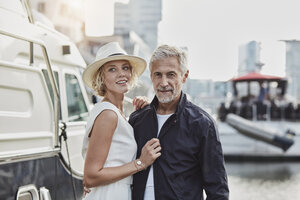 Older man and young woman at a marina next to a yacht - RORF01562