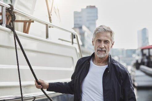 Confident mature man at a marina next to a yacht - RORF01565