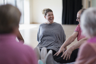 Laughing instructor and active seniors stretching legs in exercise class - CAIF21878