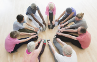 Active seniors stretching legs in circle in exercise class - CAIF21881