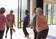 Smiling active senior women talking in exercise class - CAIF21884