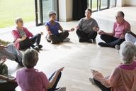 Serene active seniors meditating in circle - CAIF21902