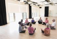 Serene active seniors meditating in circle - CAIF21905