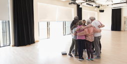 Active seniors bonding, hugging in circle in exercise studio - CAIF21908