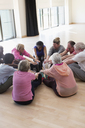 Active seniors stretching legs in circle - CAIF21911