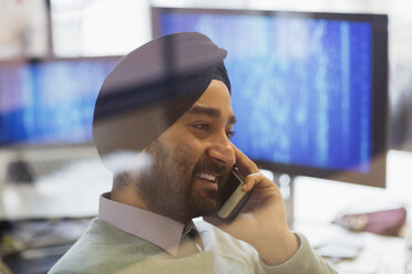 Indian computer programmer in turban talking on smart phone in office - CAIF21932