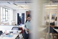 Indian businessman in turban using smart phone in office - CAIF21944