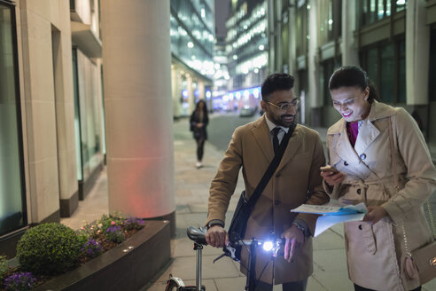 Business people with smart phone and bicycle reviewing paperwork on urban street at night - CAIF21959