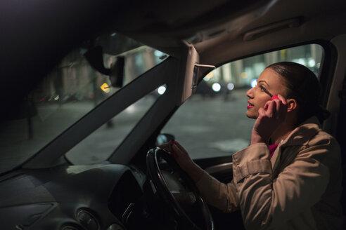 Businesswoman applying mascara in car at night - CAIF21962