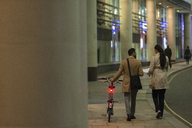 Business people with bicycle walking on urban sidewalk at night - CAIF21965