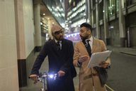 Businessmen with bicycle and paperwork walking on urban sidewalk - CAIF21968