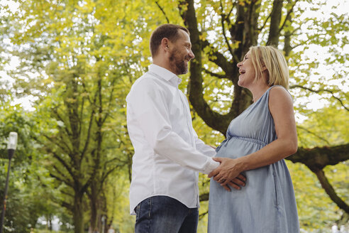 Happy mature pregnant couple talking in park - MFF04643