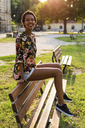 Portrait of smiling young woman sitting on bench in a park - GIOF04300