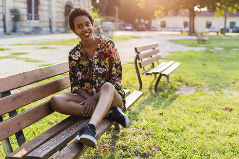 Portrait of smiling young woman sitting on bench in a park - GIOF04303