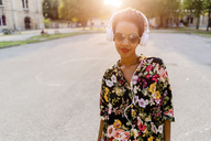 Fashionable young woman with sunglasses and headphones outdoors at sunset - GIOF04318