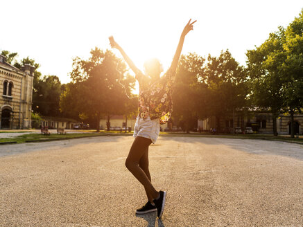 Happy fashionable young woman with headphones dancing outdoors at sunset - GIOF04321