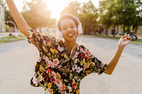 Happy fashionable young woman with headphones dancing outdoors at sunset - GIOF04324