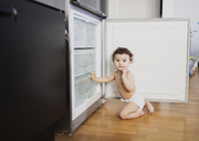 Portrait of baby boy wearing diaper crouching in front of refrigerator in the kitchen - AZOF00002