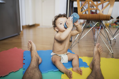 Baby boy wearing diaper sitting with his father on the floor at home drinking water - AZOF00008