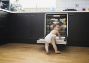 Portrait of baby boy wearing diaper exploring dishwasher in the kitchen - AZOF00011