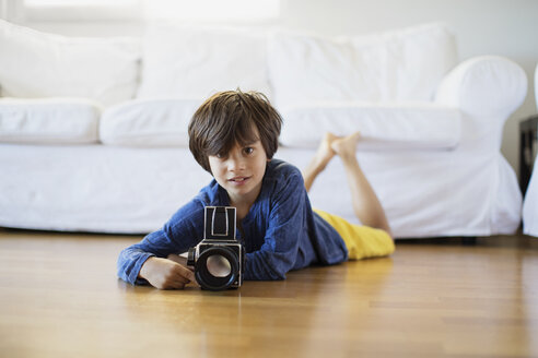 Portrait of boy lying on the floor at home with an old-fashioned film camera - AZOF00017