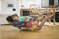 Two brothers at home lying on skateboard together having fun - AZOF00020